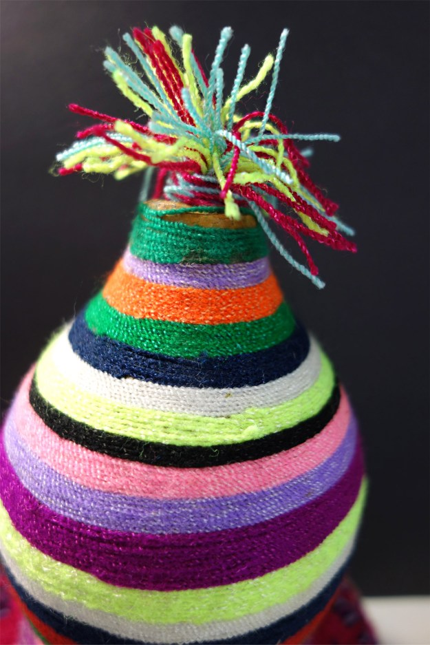 A colorful pom-pom sits on top of the gourd.