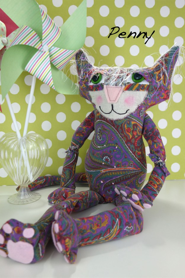 Adorable soft sculpture cat doll made out of vintage 1960's fabric. She sits in front of a green and white polka dot background and has two colorful pinwheels next to her.