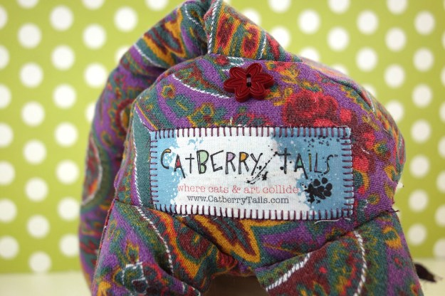 A butt shot showing the floral button under the tail and the official Catberry Tais tag.