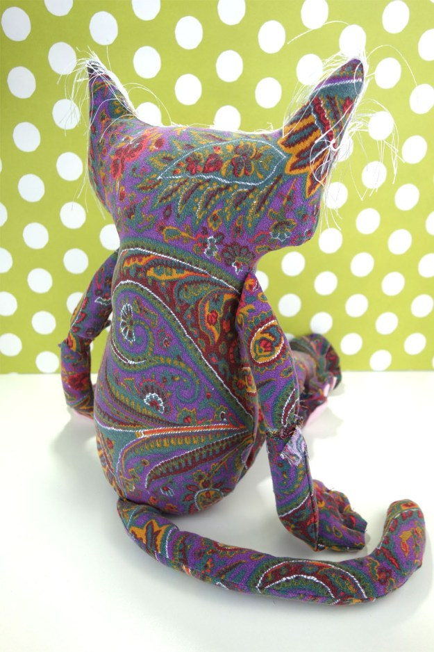 Penny is shown from the back. You can really see the paisley pattern in the vintage fabric. Her arms and paws rest by her side.