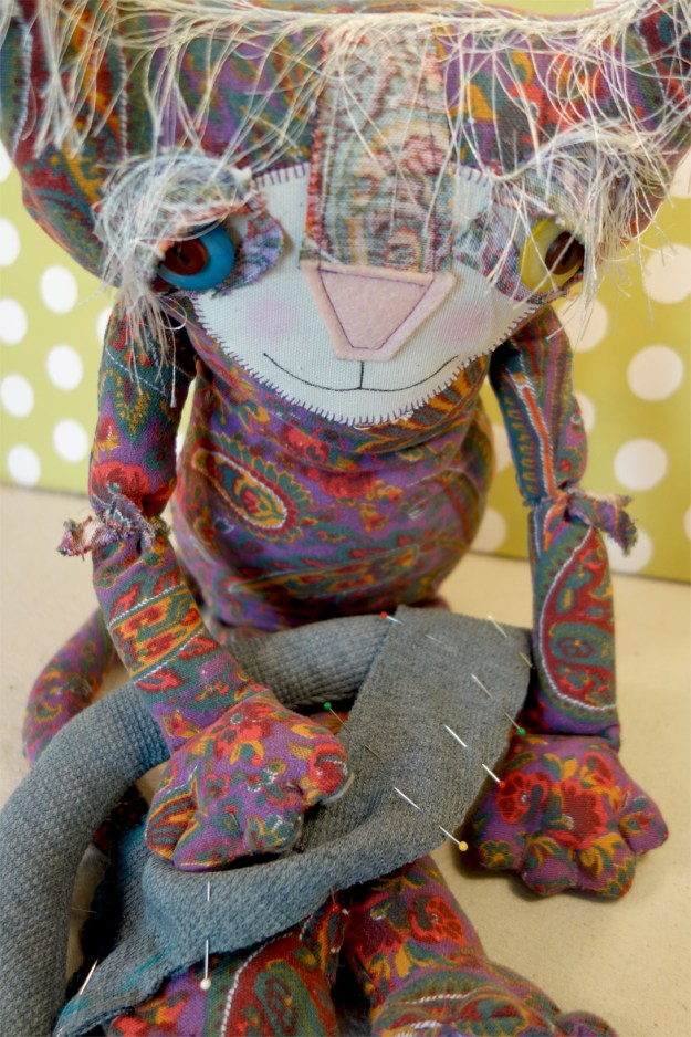 Eve, the cute soft sculpture cat doll made out of sixties paisley fabric is doing some hand sewing on a new doll.