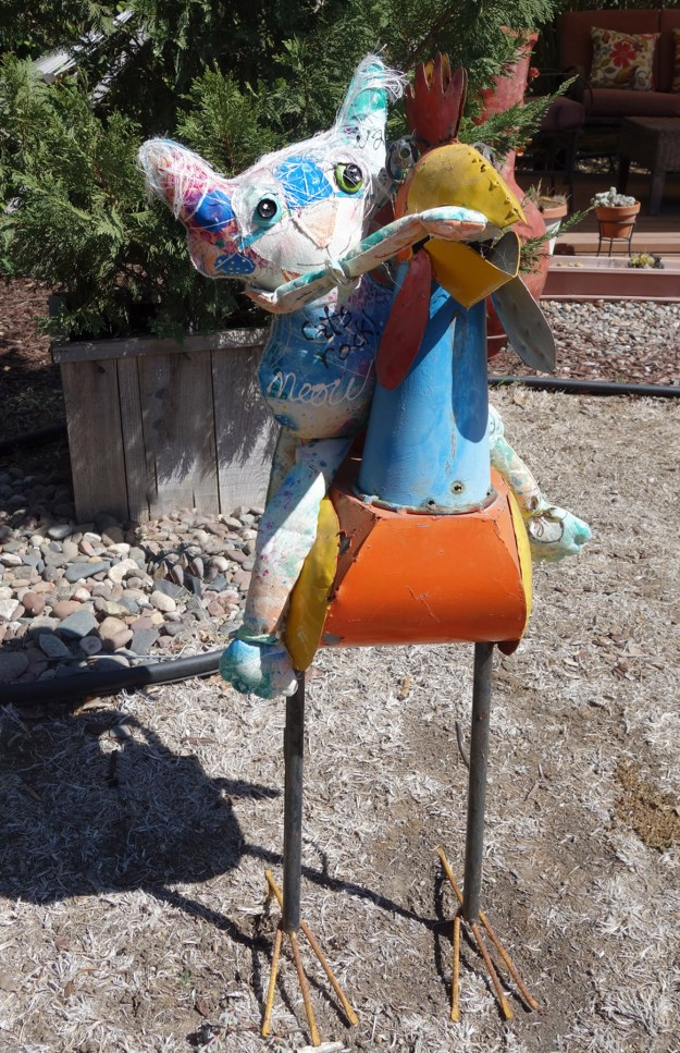 The Chairman is sitting on a large and colorful metal rooster.