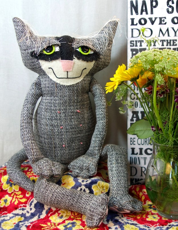 A soft sculpture cat made from an upcycled mans suit. His name is Cooper.