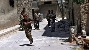 A Syrian rebel, in authenticated journalism image provided by Aleppo Media Center AMC, fires during heavy clashes Tuesday with soldiers loyal to Syrian President Bashar al-Assad near Aleppo airport.