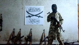 A fighter with Jamaat Ahadun Ahad. An alternate flag is featured in the back|Photograph released by the group on August 10th.