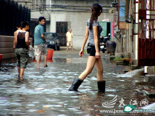 Long-legged Nanchang girl wearing boots walking in flood water