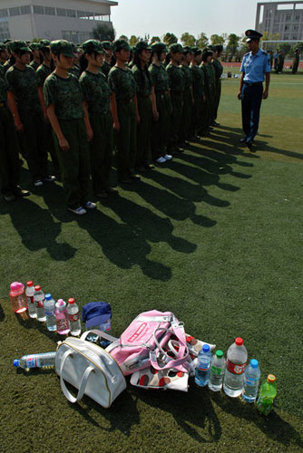 Chinese students during military training. Bags and bottles on ground.