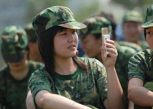 Chinese student playing with cell phone during military training.