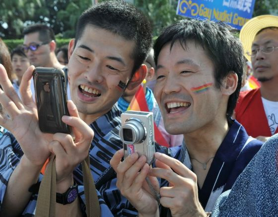 Two homosexual parade participants taking photographs for posterity.