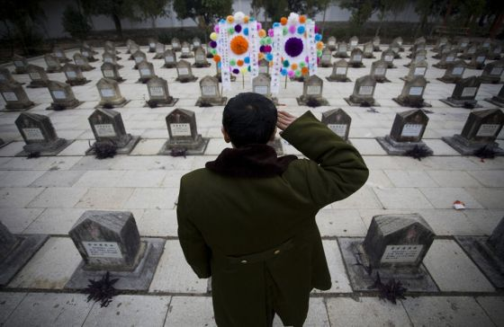 Guo Yimin salutes a small memorial for his old war friend, whom he promised to bring his remains back home