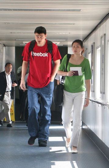 Yao Ming and Ye Li walking in airport.