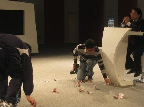 Organizers help clean up the 50 cent cash notes thrown by a student protesting the propaganda official's speech at Remin University.
