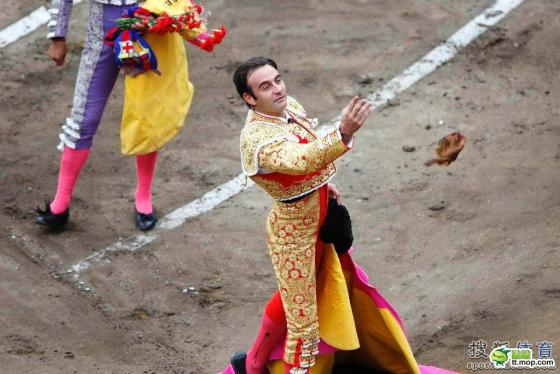 A victorious Spanish matador/bullfighter throws a rose into the audience.