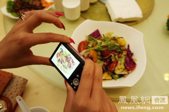Zhang Yumo photographs a salad served in a hotel she is staying at.