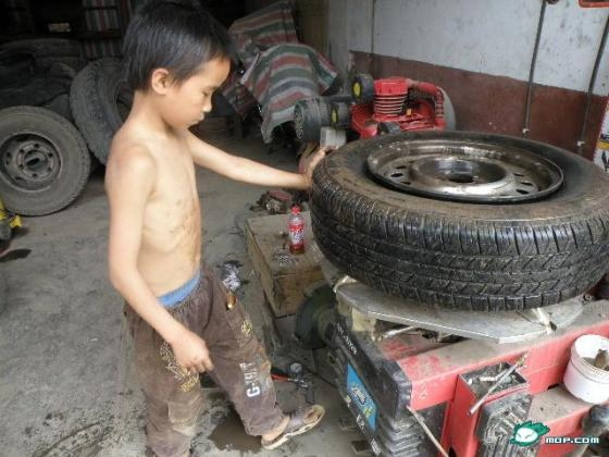A 10-year-old Chinese boy dismounts a tire.