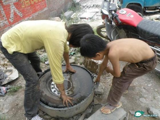 A 10-year-old Chinese boy works at a tire repair shop in China.