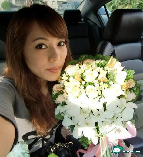 Chinese girl holding a bouquet of flowers inside a car.