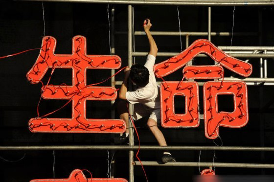 "A worker hangs between two Chinese characters for ""life""."
