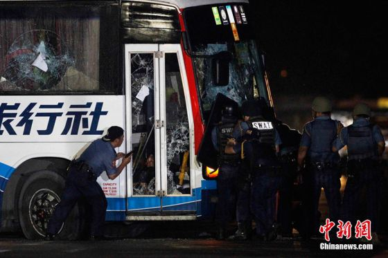 Police commandos try to open the door of a bus during the assault on a bus with tourists being held hostage at Quirino Grandstand in Manila August 23, 2010. Philippine police commandos crouched around a bus where a sacked former policeman was holding 15 Hong Kong tourists hostage in Manila on Monday and shots were heard at the scene, TV pictures and a Reuters witness said.  REUTERS/Erik de Castro