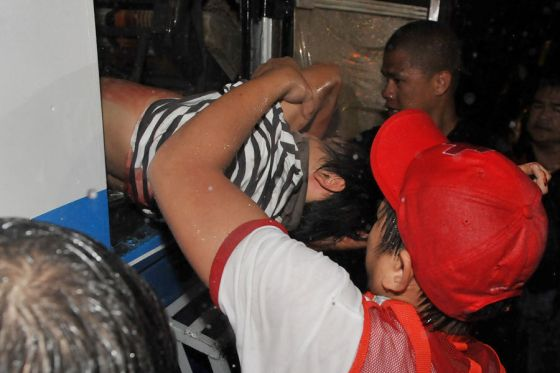 A paramedic (not pictured) lowers one of the wounded survivor from the hijacked bus in Manila on August 23, 2010.  A dramatic hostage siege in the Philippine capital involving a busload of Hong Kong tourists ended after 12 hours with several captives walking free but the fate of 11 others unknown.    AFP PHOTO / JAY DIRECTO