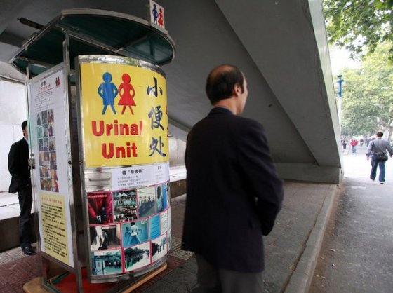 Chinese man uses unisex standing urinal in Xi'an, China.