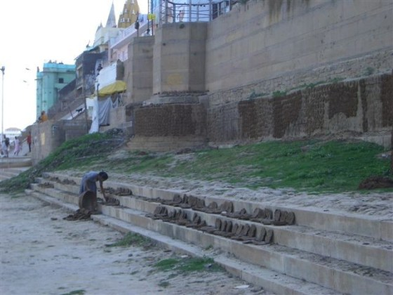 Indian woman drying cow droppings on the bank of the Ganges River.