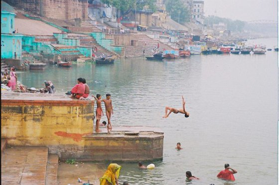 An Indian child backflips into the river water.