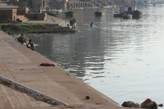A body floats by the shore of the Ganges River.