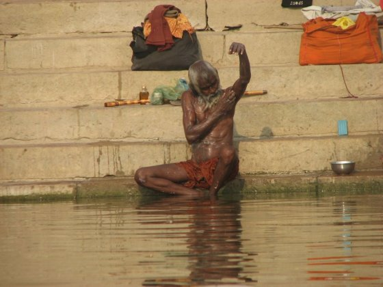 An elderly Indian bathing by the side of the Ganges River.