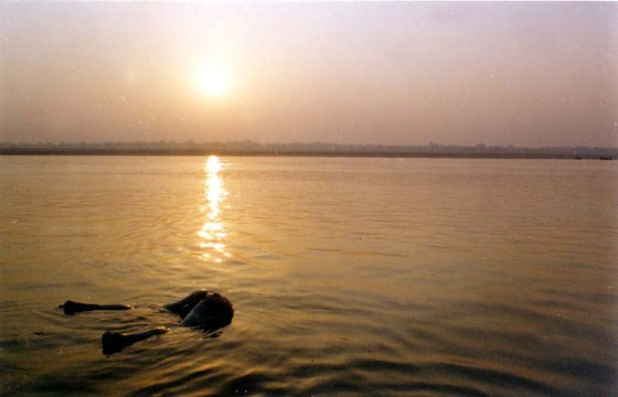 Sunset over the Ganges River, a corpse's butt floats in the water.