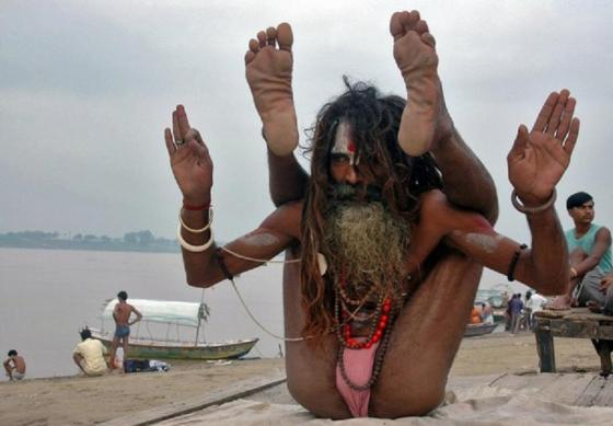 A Sadhu or holy man performs yoga on the banks of river Ganges in the northern Indian city of Allahabad June 25, 2008. Sadhus are dedicated to achieving Nirvana (liberation) through meditation and prayers by giving up three Hindu goals of life: Kama (enjoyment), Artha (practical objectives) and Dharma (duty).    REUTERS/Jitendra Prakash (INDIA)