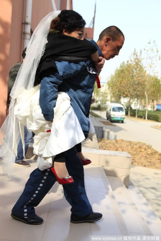 Unable to walk, the groom carries his bride.