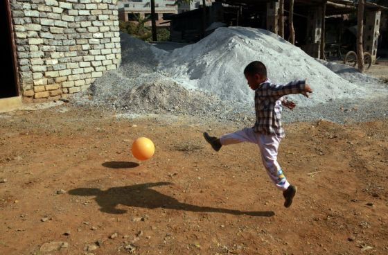 AIDS orphan A-Long kicks a ball by himself.