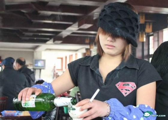 A female service staff in China serving with a cigarette in her hands.