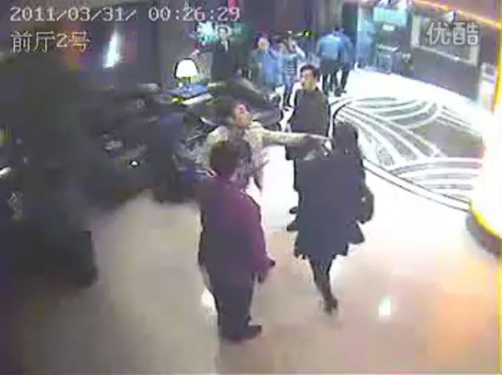 Group of men beating up a woman in a lobby in Yibin County, Sichuan province.