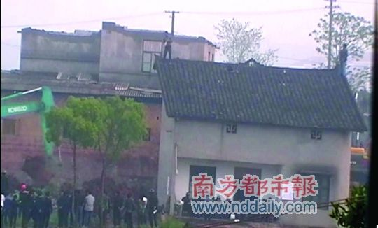Chinese man standing on roof with bottle of gasoline as an excavator approaches to tear down his house.