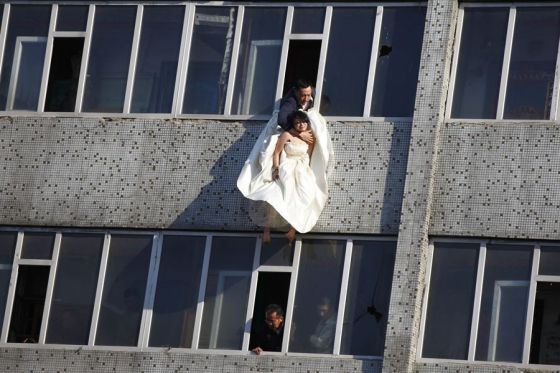 A man clutching to a young girl in a wedding dress who had just jumped out of a window trying to commit suicide.