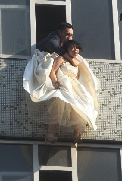 A Chinese girl in a wedding dress hangs in mid-air, a man leaning out of a window struggling to hold onto her around her neck.