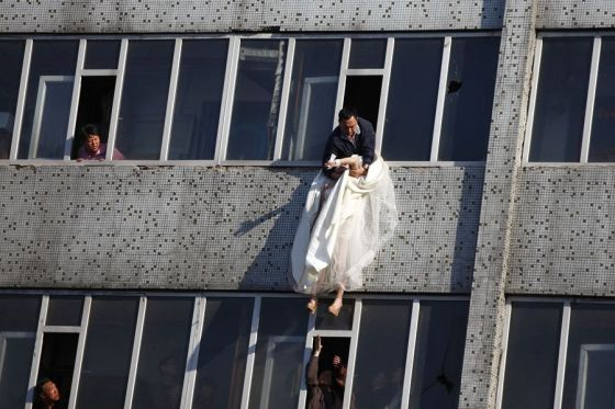 The government official struggles to pull the suicide jumping girl back through the window and safely into the building.