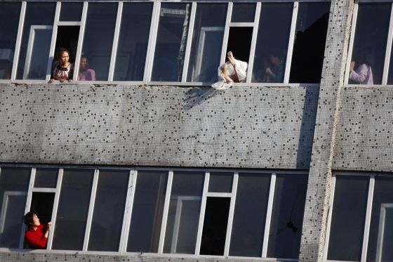 The Chinese female suicide jumper in the wedding dress finally safely pulled back through the 7th floor window and inside.