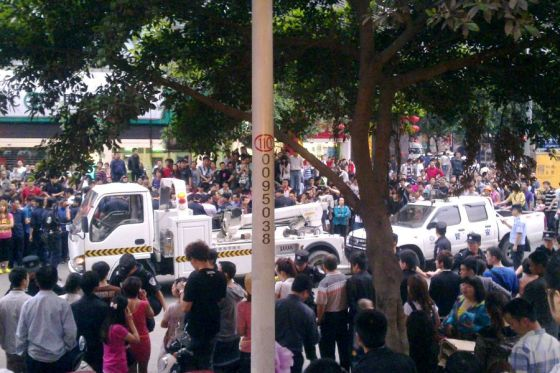 Crowds in Chengdu surround urban management officials who had beaten up an old man.