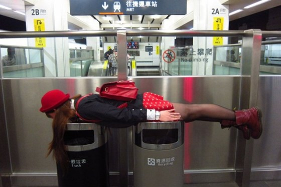 A girl in Taiwan lies stiff over a pair of garbage cans.
