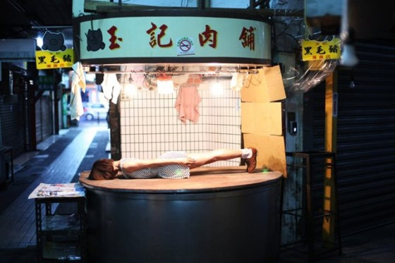 A Taiwanese girl lies flat on her face on the counter of a butchery stand in Taiwan.