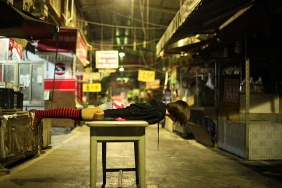 A Taiwanese girl lies face down over a table in an empty food market.