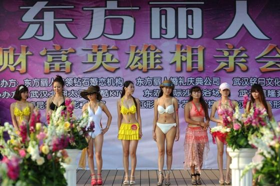 A row of women lined up on stage at a matchmaking event in Wuhan, China for rich Chinese men.