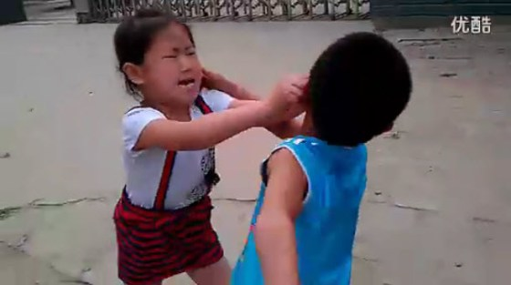A little Chinese girl fighting viciously with a little boy, her cousin, as her father films.
