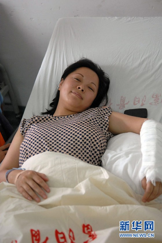Wu Juping resting in the hospital with a fractured arm sustained from catching a 2-year-old child who had fallen from a 10th floor of an apartment building.