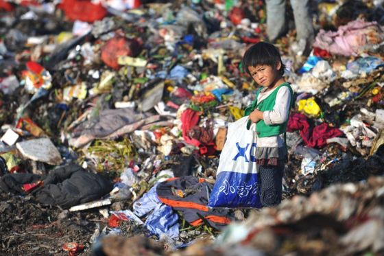 A little Chinese child scavenging for salvage and recyclables in a Guiyang landfill.
