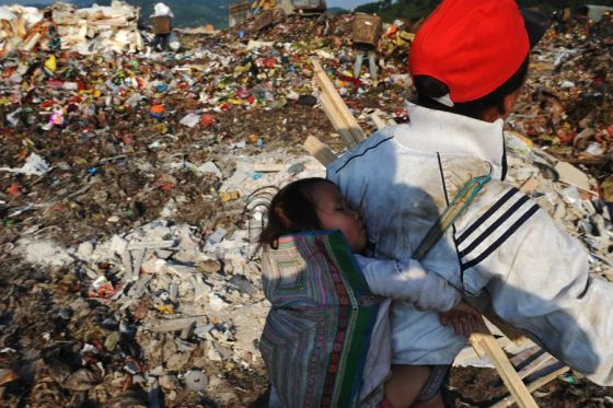 A baby on the back of her mother, a Chinese migrant worker who scavenges for recyclables and anything that can be sold from a landfill in Guiyang.