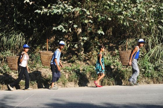 A mother and three children on their way to scavenge for recyclables and anything that can be sold for money from Guiyang's largest garbage dump.